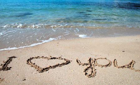 carta de amor: El amor mensaje de oro en la arena y olas del mar  Foto de archivo