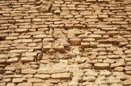 Old stone wall built of yellow limestone bricks (wall of Egyptian pyramid) Stock Photo