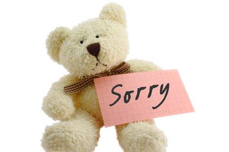 """perdonar: Vista frontal de oso de peluche de juguete con """"Lo siento"""" nota, aisladas sobre fondo blanco"""