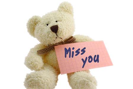 "despedida: Vista frontal de osito de juguete con ""Miss you"" nota, aislados en fondo blanco"