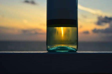 The bottle of white wine with sunset in reflection and on the background 版權商用圖片