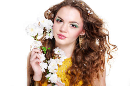 Young beautiful girl with blond curly hair holding flowers photo