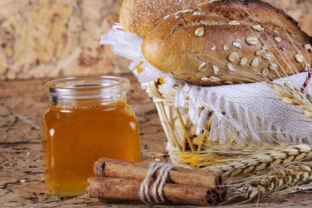 Honey and fresh bread and cinnamon on the table photo