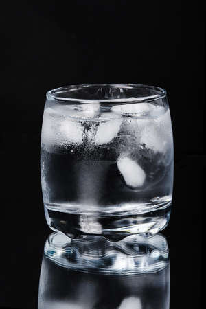taking the plunge: Glass of water with ice on a black background