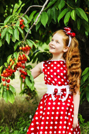 Girl in a beautiful dress in cherry garden photo