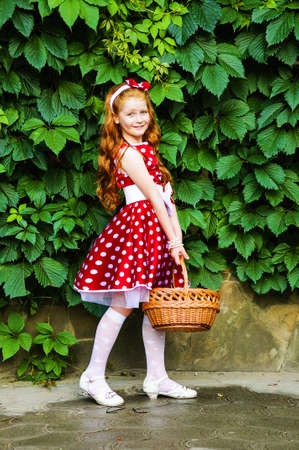 baby 4 5 years:  Girl in a beautiful dress in cherry garden Stock Photo