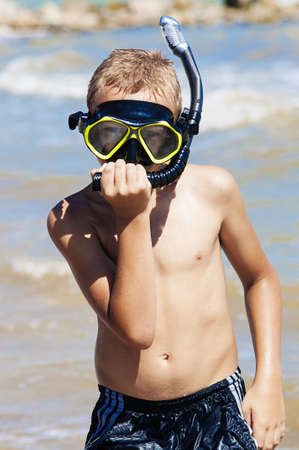 Boy in diving mask on the beach photo