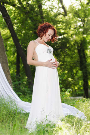 Young pregnant woman in white dress in the garden photo