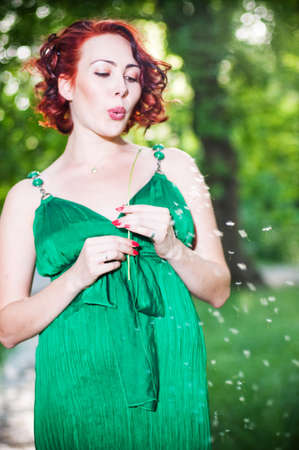 Young pregnant woman in a green dress in the garden photo