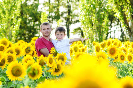 Father and boy in a sunflowers field photo