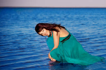 Young girl on the beach in beautiful long dress photo