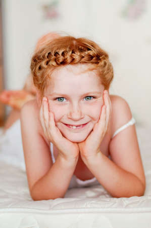 Little girl with red hair in a white dress on the bed photo