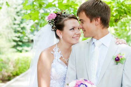 beautiful bride:  Young and beautiful bride and groom smiling at each other Stock Photo