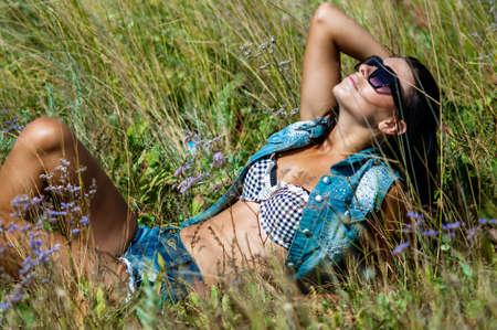 jeanswear:  Young beautiful girl in a field in jeanswear