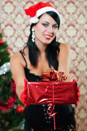 aciculum: Beautiful girl in santa hat near a christmas tree with gifts