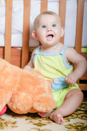 Infant baby playing on the floor at home with teddy bear photo