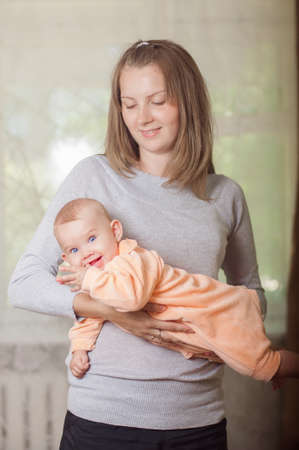 young mother holding a baby at home photo
