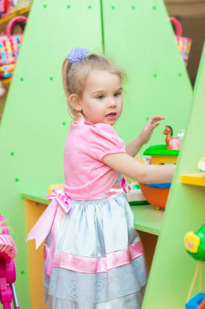 dollhouse: Little girl playing with toys in the playroom