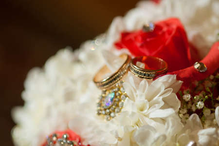 Wedding bouquet of beautiful roses and rings photo