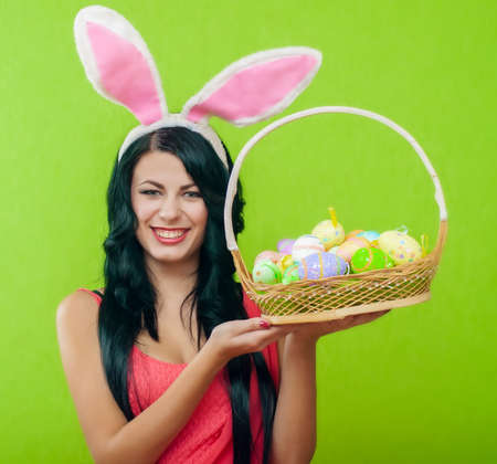 aciculum: beautiful girl with a basket of Easter eggs in a bunny suit Stock Photo