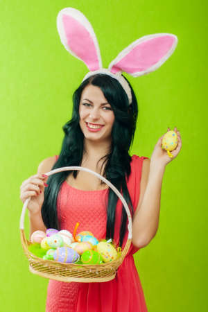 Beautiful girl with a basket of Easter eggs in a bunny suit