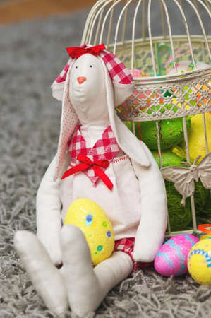 Easter toy bunny with colored eggs and decorative cell photo