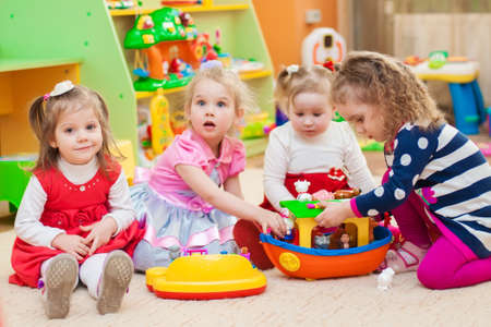 dollhouse: Little girls playing with toys in the playroom Stock Photo