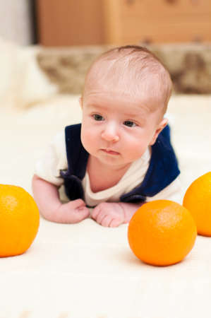 baby lying on the bed with oranges photo