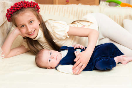 Older sister hugging baby lying on the bed at home photo