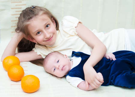 Older sister hugging baby lying on the bed with oranges photo