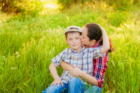 15 18: Mom and boy with dandelions in summer nature