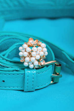 Beautiful ring of pearl and handbag on blue background photo