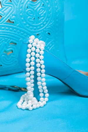 Beautiful blue shoes and handbag, pearls on blue background photo