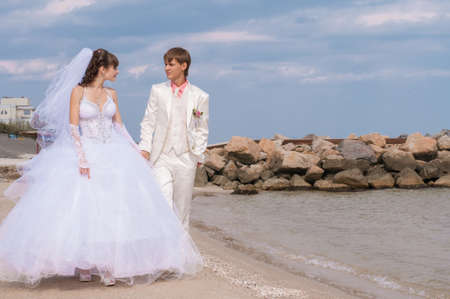 Young and beautiful bride and groom on the beach in\ summer
