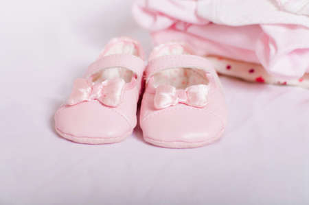 little pink baby shoes and baby clothes photo