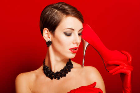 Beautiful girl with a red shoe in her hand photo