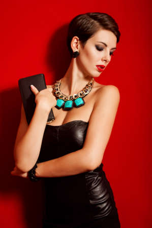 Beautiful girl with a clutch bag in her hands photo