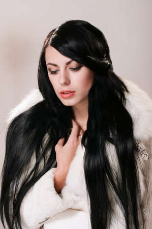 Beautiful girl with long hair in a white fur coat photo