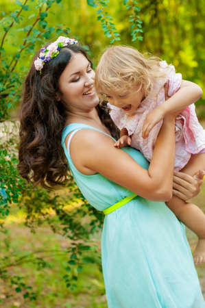 Young mother and little girl smiling outdoors photo