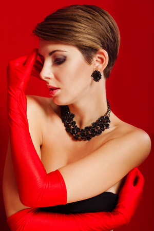 Beautiful girl in red gloves and jewelry photo