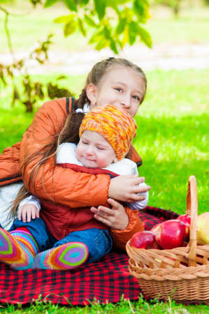 Little girl and little boy in autumn park with apples photo