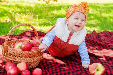 Little boy with apple in autumn park photo