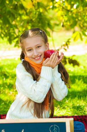 Little girl with apples in autumn park photo