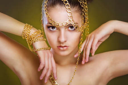 ceremonial make up: Girl with golden make-up and decoration of gold chains