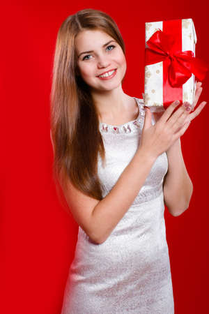 Beautiful girl with long hair with gift box in hands photo