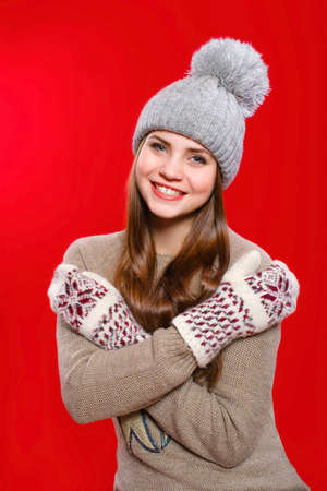 Beautiful girl in a knitted hat and gloves photo