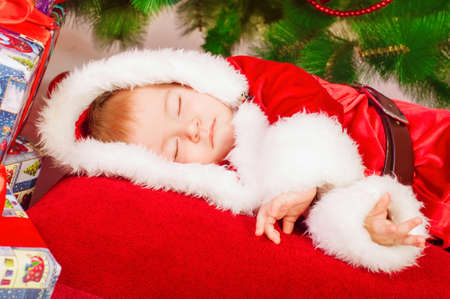 Baby in Santa costume sleeping at the Christmas tree photo