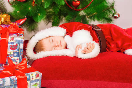 Baby in Santa costume sleeping at the Christmas tree photo
