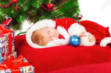 Baby in Santa costume sleeping at the Christmas tree with gifts photo