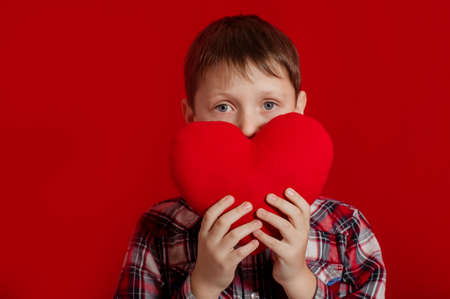little boy with a heart of toy  in hands photo